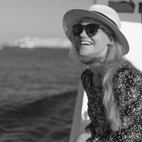 Happy blonde mediterranean woman amazed by panorama on cruise ship